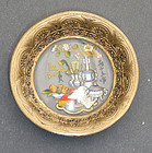 A small dish of gilt copper with carved, coloured glass