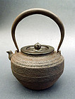 A water kettle (tetsubin) of cast iron. Lid with maker's signature.