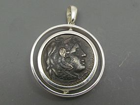 A BRONZE OBOL OF PTOLEMY II PHILADELPHOS SET IN SILVER SWIVEL PENDANT