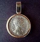 A ROMAN SILVER COIN OF EMPEROR HADRIAN SET IN 18K GOLD