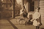 EArly photo of two sisters, a cat and a wagon