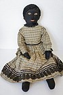 Antique black cloth doll with raised nose bead eyes nice clothes
