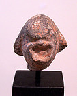 AN ANCIENT GREEK TERRACOTTA HEAD OF A COMIC ACTOR