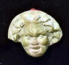 AN EGYPTO-ROMAN FAIENCE APPLIQUE OF BACCHUS