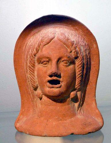 AN ETRUSCAN TERRACOTTA VOTIVE FEMALE HEAD
