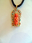 Red coral Guanyin pendant in a gold setting