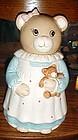 Little girl bear holding teddy bear, cookie jar