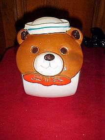 Tilted ceramic cookie jar with sailor bear face