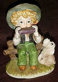 Little boy playing harmonica with hound dog figurine