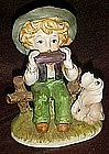 Little boy playing harmonica with hound dog figurine