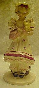 Vintage pottery girl with trunk, holding doll figurine