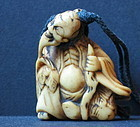 horn carving of a wise man with toad toggle pendant