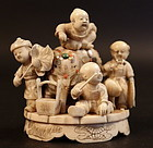 Okimono in ivory of children playing
