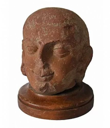 A MOTTLED RED SANDSTONE HEAD OF BUDDHA
