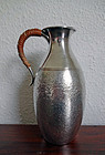 Hammered silver sake ewer with rattan handle. Late Meiji