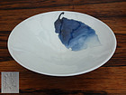 A very nice porcelain tea bowl decorated with a blue leaf.