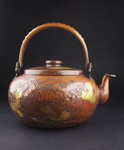 An Antique Copper Teapot with Gold Highlights