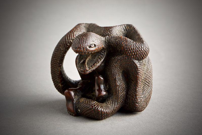A Japanese boxwood netsuke of a a woman with snake