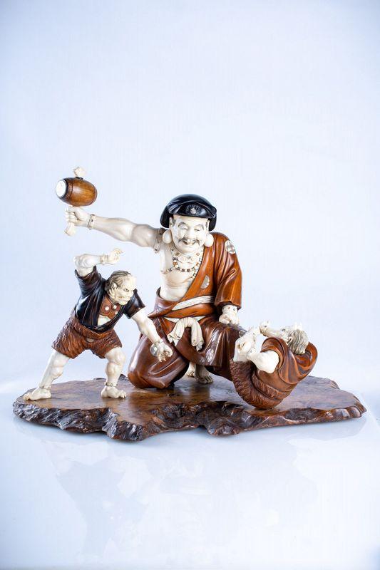 A Japanese boxwood and ivory okimono of Daikoku and two oni