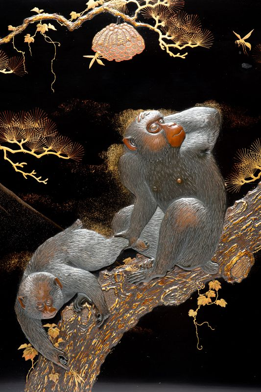 A Japanese wood lacquered painting with monkeys
