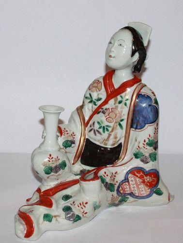A Japanese Imari figure of a Geisha holding a flower vase.