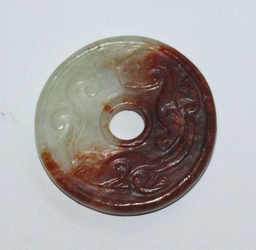 A russet and celadon jade Bi-disk.