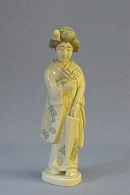 JAPANESE LATE MEIJI PERIOD IVORY OKIMONO OF A GEISHA