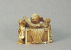 JAPANESE CARVED IVORY NETSUKE OF A SAGE READING A SCROL