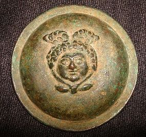 A ROMAN BRONZE ROUNDEL DEPICTING THE HEAD OF MEDUSA