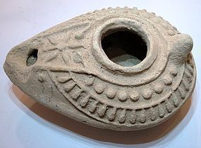 AN ISLAMIC TERRACOTTA OIL LAMP