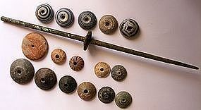 A BRONZE AGE SPINDLE AND A COLLECTION OF SPINDLE WHORLS