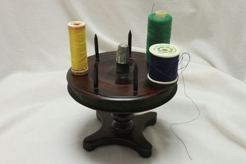 Revolving cotton reel holder in the shape of a table