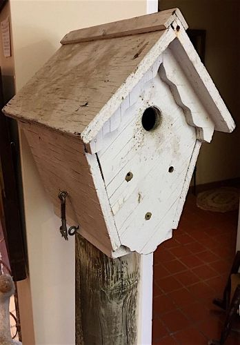 Vintage folk art wooden bird house on tall post base