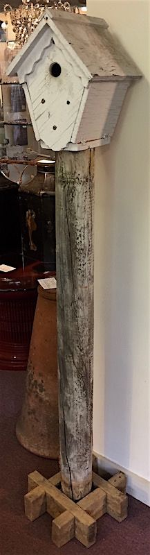 Vintage folk art wooden bird house on tall post base