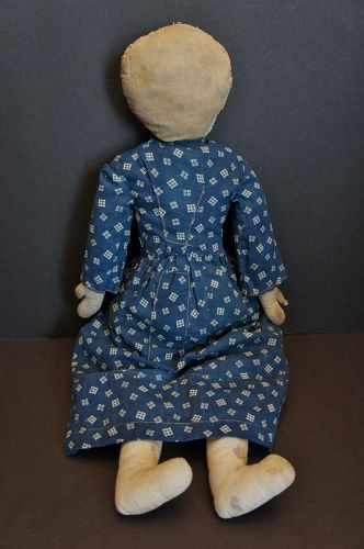 A pencil face doll with big eyes wearing a blue calico dress