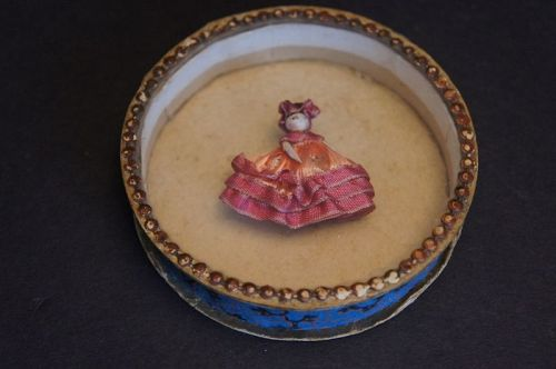 Miniature wooden penny doll in round Dresden wallpapered box