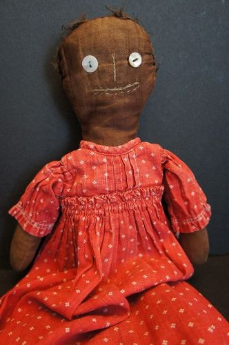 A funny little antique black cloth doll in red calico dress