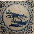 A blue and white hand painted wall tile of a dog rising up on its hind