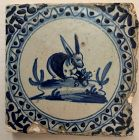 Delft blue and white wall tile of a seated rabbit 17th century
