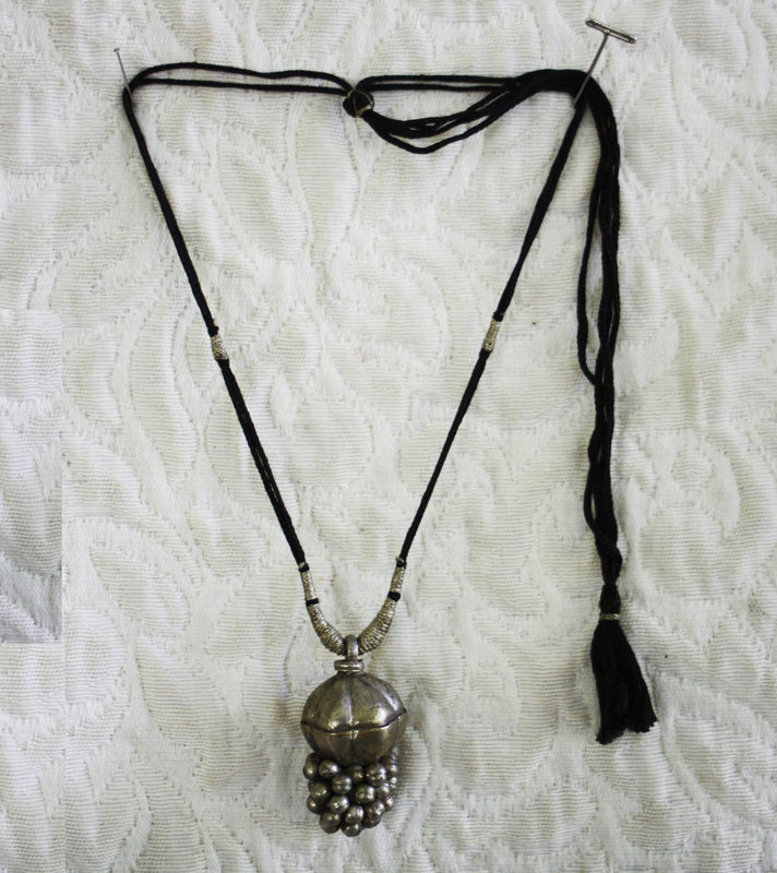 India woman's necklace with silver Lingam stone casket