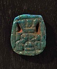 AN ANCIENT EGYPTIAN BLUE FAIENCE BES AMULET
