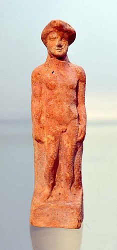 AN ANCIENT GREEK TERRACOTTA MALE FIGURINE