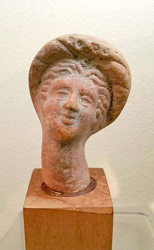 AN ANCIENT GREEK TERRACOTTA FEMALE HEAD
