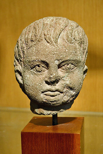 AN ETRUSCAN LIMESTONE HEAD OF A YOUNG BOY