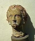 AN ANCIENT GREEK TERRACOTTA FEMALE HEAD