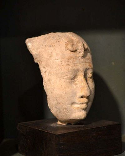 AN EGYPTIAN PAINTED LIMESTONE  HEAD OF A PHARAOH