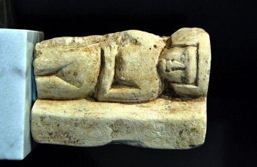 AN ANCIENT EGYPTIAN RECLINING LIMESTONE FEMALE
