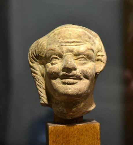 AN EGYPTO=ROMAN TERRACOTTA HEAD OF HARPOCRATES