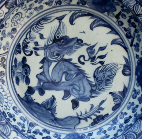 A MING DYNASTY BLUE AND WHITE DISH WITH QIRIN