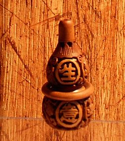 Carved wooden toggle with four Chinese characters
